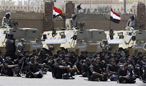 Riot police and army soldiers are seen outside the police academy where a trial is being held for those accused of involvement in a soccer stampede, on the outskirts of Cairo