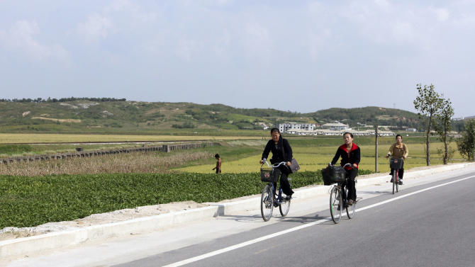 In this photo taken on Sept. 21, 2012 photo, young North Koreans cycle along a road that leads from the Kaesong industrial complex near the Demilitarized Zone to downtown Kaesong, North Korea. Since April 3, North Korean authorities have barred South Koreans from entering North Korea through the Demilitarized Zone to get to the Kaesong industrial complex where some 120 South Korean companies run factories employing North Korean workers. (AP Photo/Jean H. Lee)
