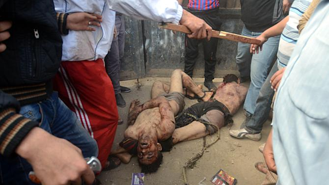 EDS NOTE GRAPHIC CONTENT -- Egyptian men, one holding a knife and another a bloody stick, surround the bodies of two men who were beaten and hung by vigilantes after being accused of theft in the small Nile Delta town of Samanod, about 55 miles (90 kilometers) north of Cairo, Egypt, Sunday March 17, 2013. Egyptian vigilantes beat two men accused of stealing a motorized rickshaw, then stripped them half-naked and hung them still alive in a bus station in a small Nile Delta town on Sunday, according to security officials who said both men died. The killings came a week after the attorney general's office encouraged civilians to arrest lawbreakers and hand them over to police. (AP Photo)
