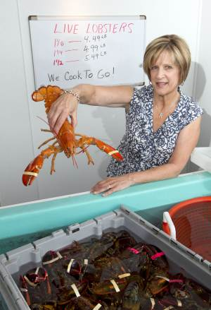 In this photo made Thursday, June 28, 2012, Paula Coppersmith holds a lobster at Dock's Seafood restaurant and market in South Portland, where they're selling five lobsters for $24. Many stores are selling the king of seafood for under $5 a pound, making it cheaper than bologna by weight. (AP Photo/Robert F. Bukaty)