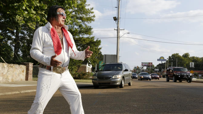Elvis Presley impersonator Dennis Nickells, from Vernon, N.Y., performs for drivers on Elvis Presley Boulevard in front of Graceland, Presley's Memphis, Tenn. home, on Wednesday, Aug. 15, 2012. Presley fans from around the world are at Graceland to take part in the annual candlelight vigil marking the 35th anniversary of his death. (AP Photo/Mark Humphrey)