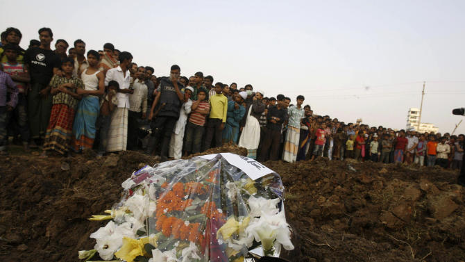 FILE - In this Tuesday, Nov. 27, 2012 file photo, hundreds of Bangladeshi mourners watch as the bodies of a part of the victims of Saturday's fire in a garment factory are buried in Dhaka, Bangladesh. A Dhaka fire official said the Tazreen factory's fire safety certification had expired on June 30, and fire officials refused to renew it because the building did not have the proper safety arrangements. The factory did not have any fire exits for its 1,400 workers, many of whom became trapped by the blaze. Investigators said the death toll would have been far lower if there had been even a single emergency exit. (AP Photo/Pavel Rahman)
