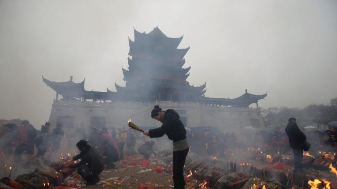 Worshippers burn incense to pray for wealth on the fifth day of Chinese Lunar New Year at Guiyuan Buddhist Temple in Wuhan