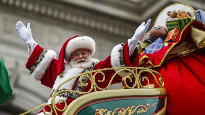 A man dressed as Santa Claus waves as he rides on his float down Central Park West during the 88th Macy's Thanksgiving Day Parade in New York