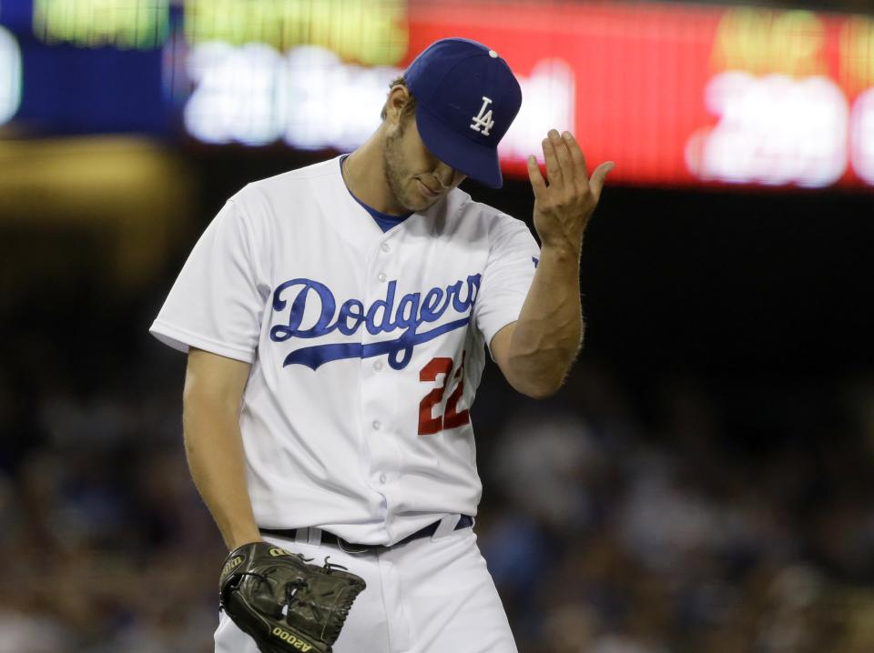 Los Angeles Dodgers pitcher Clayton Kershaw gestures to first base umpire Alfonso Marquez, after he was called for a balk, against the Washington Nationals in the third inning of a baseball game in Los Angeles Tuesday, May 14, 2013. (AP Photo/Reed Saxon)