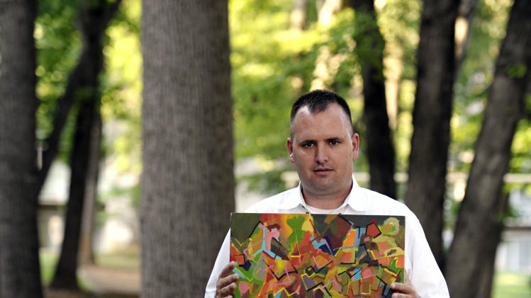 In this Aug. 23, 2012 photo, Kevin Earley, 33, displays one of his paintings outside his Vienna, Va., apartment that he shares with a roommate. Earley, who suffers with a mental health condition, works full time as a peer counselor in Fairfax County, Va., helping others with severe mental illnesses. (AP Photo/Cliff Owen)