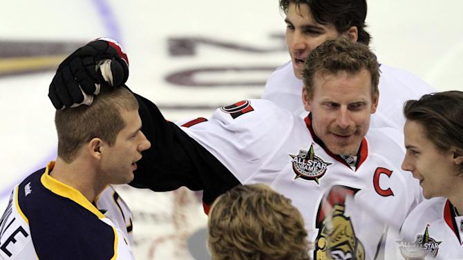 Ottawa Senators' Daniel Alfredsson (11) celebrates with Buffalo Sabres' Jason Pominville  (29) as other members of Team Alfredsson look on at the NHL All Star Skills hockey competition in Ottawa, Ontario, on Saturday, Jan. 28, 2012.  (AP Photo/The Canadian Press, Fred Chartrand)