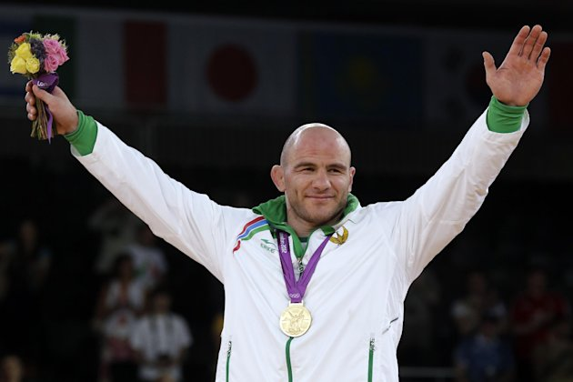 Gold medalist Artur Taymazov of Ukbekistan is presented the medal during the victory ceremony for the men's 120-kg freestyle wrestling competition at the 2012 Summer Olympics, Saturday, Aug. 11, 2012, in London. (AP Photo/Paul Sancya)