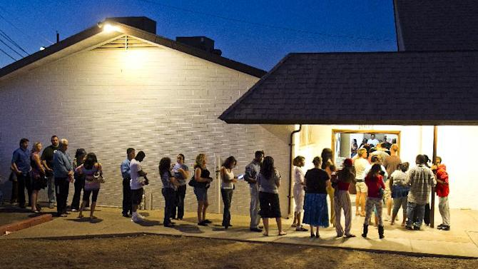 """--FILE--People wait in line to vote at polling place located in a church in Phoenix in this Nov. 6, 2012, file photo. The Supreme Court ruled Monday, June 17, 2013, that states cannot on their own require would-be voters to prove they are U.S. citizens before using a federal registration system designed to make signing up easier. The justices voted 7-2 to throw out Arizona's voter-approved requirement that prospective voters document their U.S. citizenship in order to use a registration form produced under the federal """"Motor Voter"""" voter registration law. (AP Photo/The Arizona Republic, Tom Tingle) MARICOPA COUNTY OUT; MAGS OUT; NO SALES"""