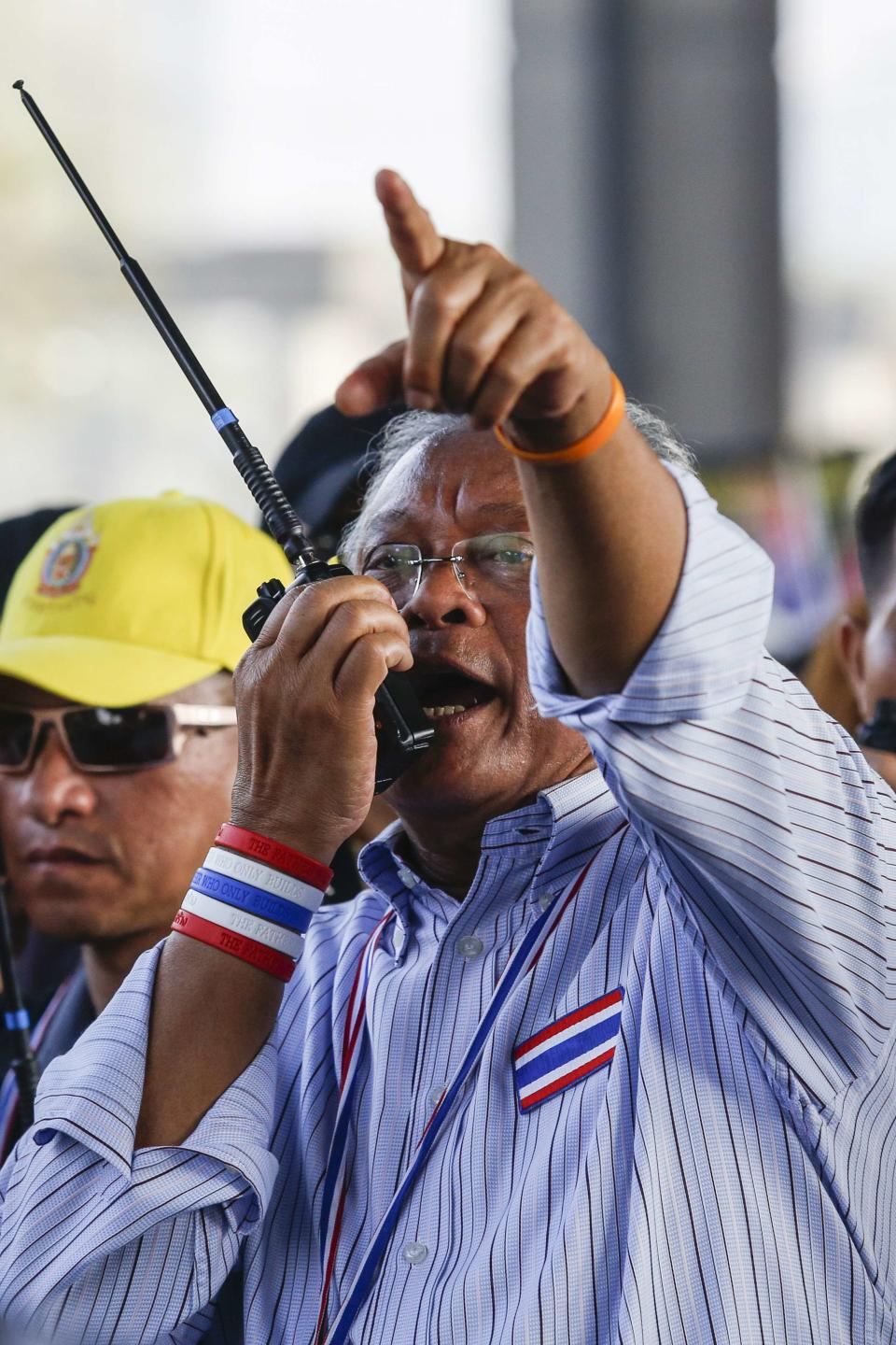 Protest leader Suthep talks into a radio transceiver during a rally in Bangkok