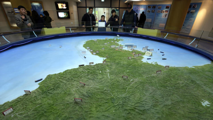 "Visitors look at a giant relief map of Korean Peninsular at the unification observation post near the border village of Panmunjom, that has separated the two Koreas since the Korean War, in Paju, north of Seoul, South Korea, Saturday, March 30, 2013. North Korea issued its latest belligerent threat Saturday, saying it has entered ""a state of war"" with South Korea a day after its young leader threatened the United States because two American B-2 bombers flew a training mission in South Korea. (AP Photo/Lee Jin-man)"
