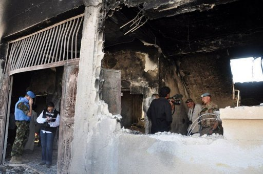 UN observers inspect a bombarded school in the Syrian village of Treimsa
