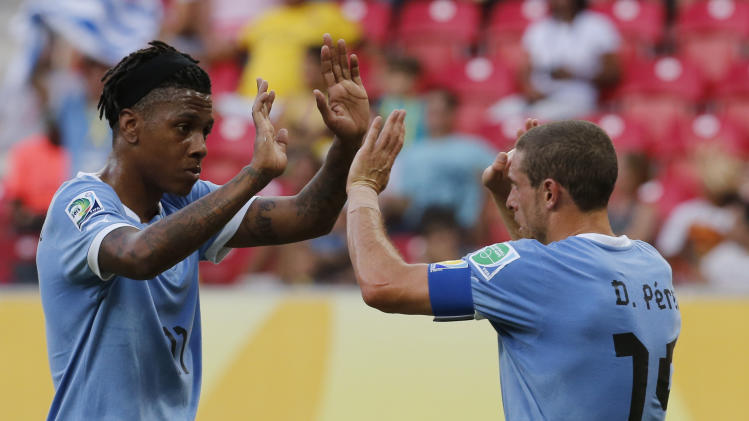 Uruguay's Diego Perez celebrates with teammate Abel Hernandez after scoring his side's third goal during a soccer Confederations Cup group B match against Tahiti at the Arena Pernambuco in Recife, Brazil, Sunday, June 23, 2013. (AP Photo/Eugene Hoshiko)