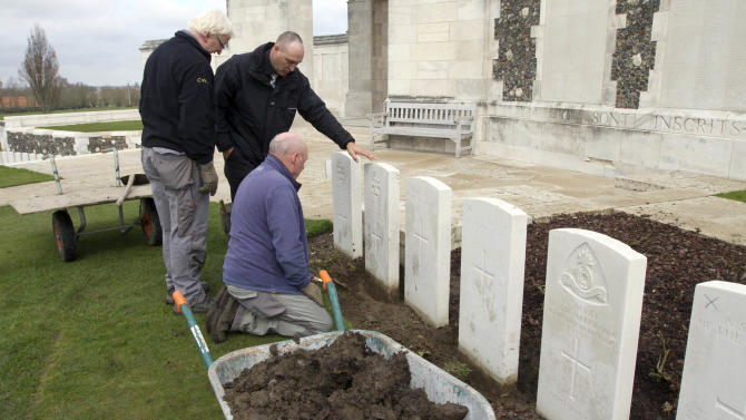 A group of workers for the Commonwealth War Graves Commission discuss the removal of a row of damaged WWI headstones at Tyne Cot cemetery in Zonnebeke, Belgium on Monday, April 15, 2013. With nearly 12,000 graves the cemetery is the largest Commonwealth war cemetery in the world in terms of burials. The damaged headstones will be removed and replaced with newly engraved stones in preparation for the upcoming centenary which begins in 2014. (AP Photo/Virginia Mayo)