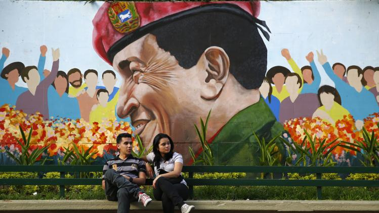 A couple sits in a park next to a mural of late Venezuela's president Hugo Chavez in Caracas