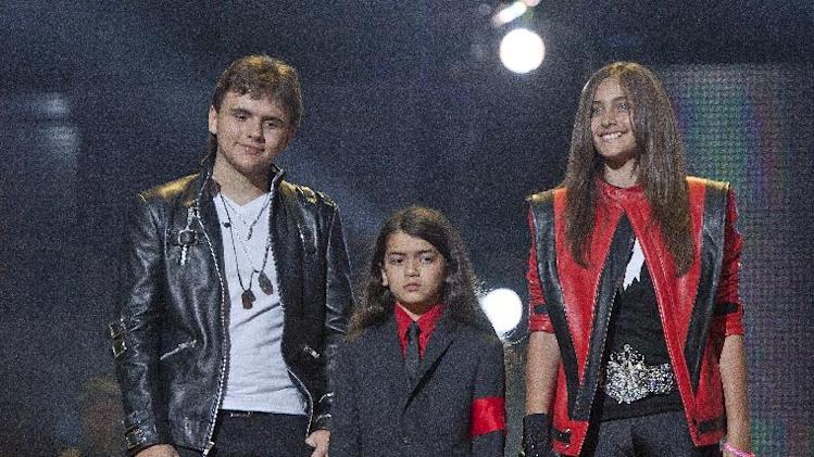"FILE - In this Oct. 8, 2011 file photo, from left, Prince Jackson, Prince Michael II ""Blanket"" Jackson and Paris Jackson arrive on stage at the Michael Forever the Tribute Concert, at the Millennium Stadium in Cardiff, Wales. TJ Jackson, one of Michael's favorite nephews, has been designated to work beside Michael's mother, Katherine, to look after the welfare of his three cousins Prince, 15, Paris, 14 and Blanket,10, who will inherit the King of Pop's fortune. (AP Photo/Joel Ryan, File) *Editorial Use Only*"