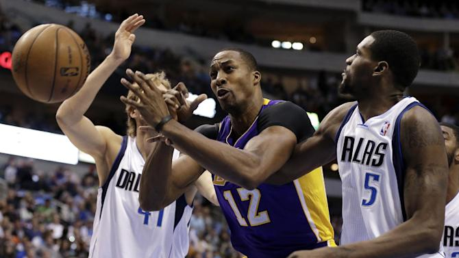 Los Angeles Lakers' Dwight Howard (12) loses control of the ball fighting for a shot attempt against Dallas Mavericks' Bernard James (5) and Dirk Nowitzki, left rear, in the first half of an NBA basketball game Sunday, Feb. 24, 2013, in Dallas. (AP Photo/Tony Gutierrez)