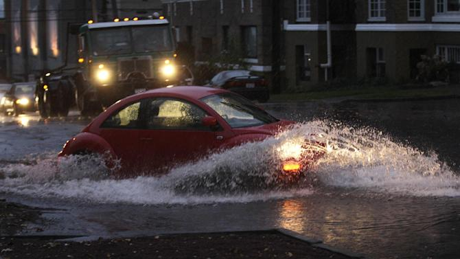 Cars and trucks navigate through standing water, Monday, Nov. 19, 2012, at an intersection in Tacoma, Wash. Wet and windy weather with mountain snow will continue this week in Washington, forecasters said. (AP Photo/Ted S. Warren)