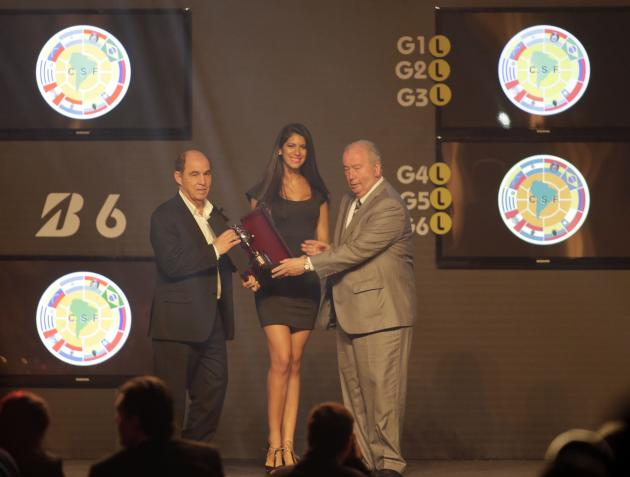 Argentina's former soccer player Hector Ricardo Bochini receives an award from President of the Argentine Football Association (AFA) Julio Grondona during the draw for the 2014 Copa Libertadores a