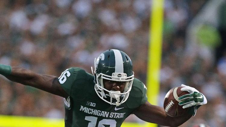 Michigan State's Aaron Burbridge (16) hurdles Jacksonville State's Folo Johnson (4) during the first quarter of an NCAA college football game, Friday, Aug. 29, 2014, in East Lansing, Mich