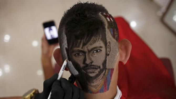 Hair artist and barber Nariko, etches the image of Barcelona's Neymar, on the head of customer Fernadez, at his barbershop in Sao Vicente