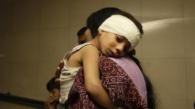 A Pakistani mother holds her injured child at a local hospital in Karachi, Pakistan  on Wednesday, Nov. 21, 2012. Two bombs exploded outside a Shiite mosque in the southern city of Karachi, killing scores of people and wounding others in a suicide attack, police official said. (AP Photo/Fareed Khan)