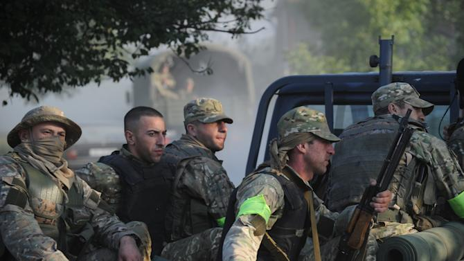 Georgian servicemen ride along a road at the village of Lapankuri, some 175 km (108 miles) east of Tbilisi Wednesday, Aug. 29, 2012. Georgian troops blocked a gorge on the Georgian-Russian state border where an unknown armed group was detected on Wednesday, according to an Internal Affairs Ministry statement. (AP Photo/ Irakli Gedenidze, Pool)