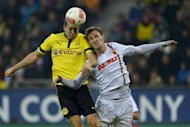 FC Augsburg's defender Sebastian Langkamp (R) and Dortmund's striker Robert Lewandowski jump for the ball during their German Bundesliga football match in Augsburg, southern Germany. Dortmund won 3-1