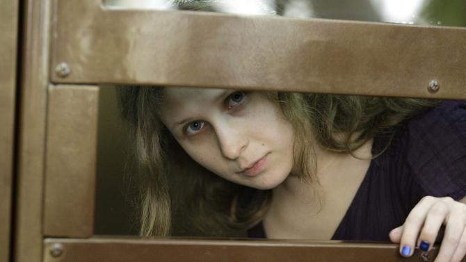"""Yekaterina Samutsevich member of feminist punk group Pussy Riot looks on as she stand behind bars in a court in Moscow, Russia, Russia, Monday, July 30, 2012. Three members of the band are facing trial for performing a """"punk prayer"""" against Vladimir Putin from a pulpit of Moscow's main cathedral before Russia's presidential election in March, in which he won a third term. (AP Photo/Mikhail Metzel)"""