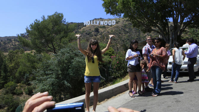 In this July 13, 2011 photo, tourists photograph each other on a hill with a view of the Hollywood sign in Los Angeles. With more than 50 miles of free hiking trails, many of them winding through chaparral-covered canyons and over hillsides, Griffith Park bills itself as the largest urban wilderness in the United States.  (AP Photo/Damian Dovarganes, File)