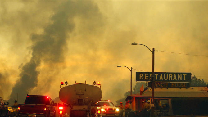 Firefighters monitor a restaurant as the Yarnell Hill Fire burns on Sunday, June 30, 2013 near Yarnell, Ariz. The fire started Friday and picked up momentum as the area experienced high temperatures, low humidity and windy conditions. It has forced the evacuation of residents in the Peeples Valley area and in the town of Yarnell. (AP Photo/The Arizona Republic, David Kadlubowski)