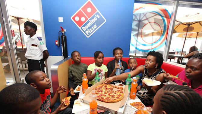 In this photo taken Sunday, Feb. 10, 2013 a family eats Domino's pizza at a restaurant in Lagos, Nigeria. As Nigeria's middle class grows along with the appetite for foreign brands in Africa's most populous nation, more foreign restaurants and lifestyle companies are entering the country. And the draw on Nigerians' new discretionary spending has also put new expectations on providing quality service in a nation where many have grown accustomed to expecting very little. ( AP Photo/Sunday Alamba)
