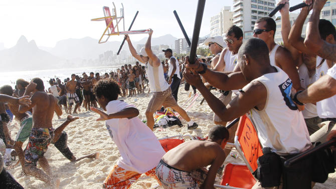 """In this Nov. 20, 2013 photo, municipal guards chase a gang of thieves that robbed bags and wallets from beachgoers on Arpoador beach in Rio de Janeiro, Brazil. Gang raids known as """"arrastoes,"""" or """"big drags"""" in Portuguese, spread alarm through a city gearing up to host soccer's World Cup in just over six months and the Summer Olympics in 2016. (AP Photo/Marcelo Carnaval, Agencia o Globo)"""