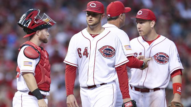 Cincinnati Reds starting pitcher Josh Smith, right, is taken out of the game after hitting Milwaukee Brewers' Carlos Gomez with a pitch in the fifth inning of a baseball game, Saturday, July 4, 2015, in Cincinnati. The Brewers won 7-3. (AP Photo/John Minchillo)