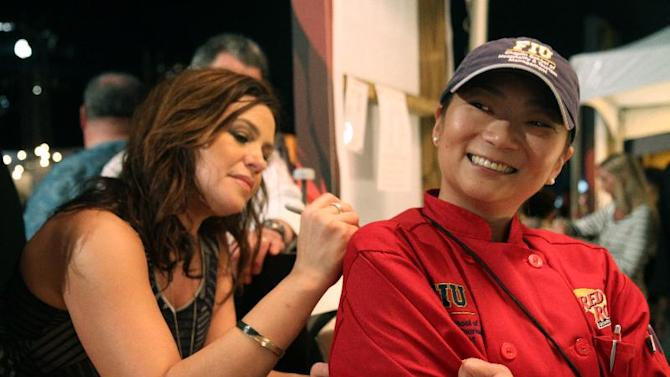 IMAGE DISTRIBUTED FOR RED ROBIN - Rachel Ray, left,  takes a break from her hosting duties at the Amstel Light Burger Bash at the Food Network South Beach Wine and Food Festival to sign an autograph for Luciana Page, the Florida International University student who earned the opportunity to serve her Korean Kalbi BBQ Burger at the festival on Feb. 22, 2013 after winning Red Robin's Savory Scholar Contest.  (Photo by Marianela Sanchez/Invision for Red Robin/AP Images)