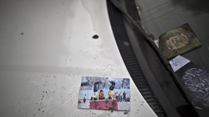 A picture showing schoolchildren playing is left on a car, inside the Army Public School attacked last Tuesday by Taliban gunmen, in Peshawar, Pakistan. (AP Photo/Muhammed Muheisen)