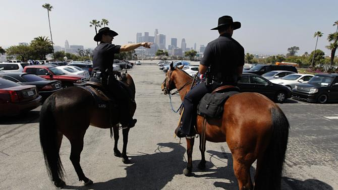Members of the Los Angeles Police Department's mounted patrol work the parking lot before a baseball game between the Los Angeles Dodgers and the Pittsburgh Pirates in Los Angeles, Tuesday, April 10, 2012.  Police were out in force for opening day at Dodger Stadium, swarming on bikes, going undercover and looking for boozing tailgaters a year after a Giants fan was beaten into a coma in the parking lot.(AP Photo/Chris Carlson)