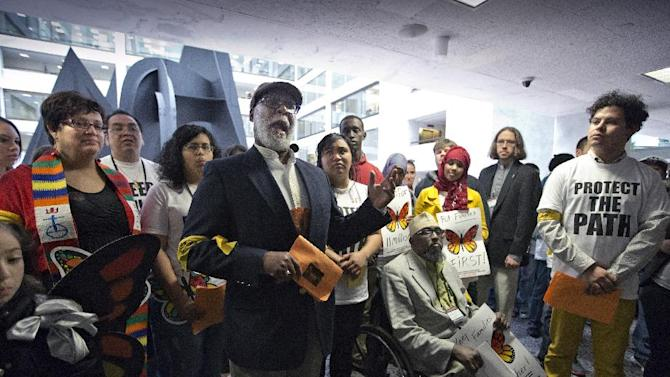 Rev. Eugene Barnes of Champaign, Ill., and president of Illinois People's Action, joins immigration advocates gathered outside the Senate Judiciary Committee hearing on immigration reform in the Senate Hart Office Building on Capitol Hill in Washington, Monday, April 22, 2013, to recount personal stories of how they were affected by being undocumented in America. (AP Photo/J. Scott Applewhite)