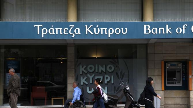 People pass outside of a branch of bank of Cyprus at a main shopping street in capital Nicosia, Cyprus, Wednesday, April 17, 2013. A prominent European Parliament lawmaker scolded Cyprus' bailout creditors on Wednesday for failing to insist on the ethnically-split country's reunification that he says could boost growth through stronger business ties with neighboring Turkey. (AP Photo/Petros Karadjias)wld