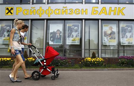 Pedestrians walk past a Raiffeisen Bank branch in Moscow