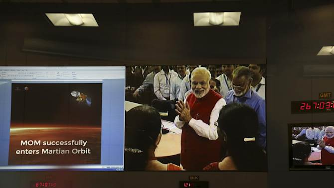 Screens show Indian Prime Minister Narendra Modi greeting Indian Space Research Organisation scientists and other officials after the success of Mars Orbiter Mission at their Telemetry, Tracking and Command Network complex in Bangalore, India, Wednesday, Sept. 24, 2014. India triumphed in its first interplanetary mission, placing a satellite into orbit around Mars on Wednesday morning and catapulting the country into an elite club of deep-space explorers. (AP Photo/Aijaz Rahi)