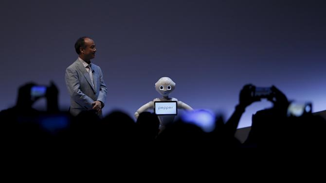 "People take pictures of SoftBank Group Corp. Chairman and CEO Son and SoftBank's human-like robots named ""Pepper"" during the SoftBank World 2015 event in Tokyo"
