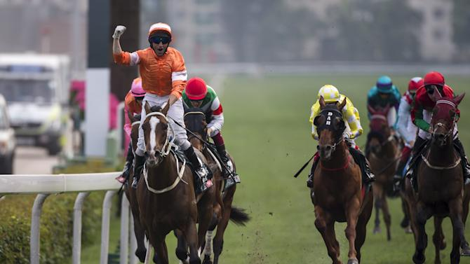 Irish jockey Callan celebrates on Blazing Speed after crossing the finish line to win the 2,000m Audemars Piguet Queen Elizabeth II Cup Group One race at Sha Tin Racecourse in Hong Kong