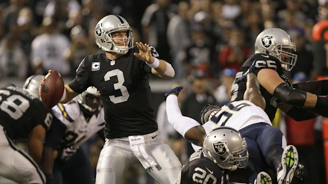 Oakland Raiders quarterback Carson Palmer (3) passes as running back Darren McFadden (20) upends San Diego Chargers linebacker Donald Butler (56) during the first quarter of an NFL football game in Oakland, Calif., Monday, Sept. 10, 2012. (AP Photo/Jeff Chiu)