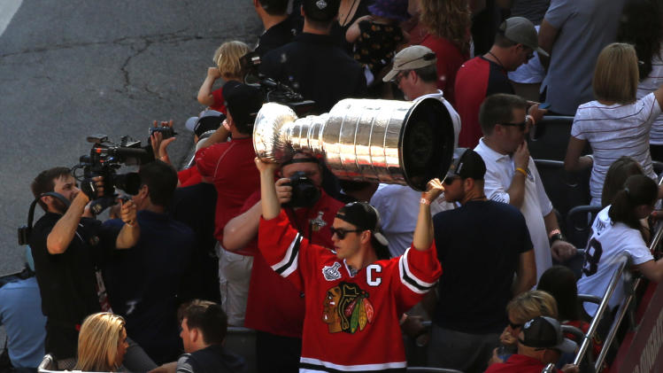 Chicago Blackhawks' Jonathan Toews holds up the 2013 Stanley Cup during a victory parade down Washington Street Friday, June 28, 2013 in Chicago. The Blackhawks celebrate the team's second championship in four years. (AP Photo/Charles Rex Arbogast)