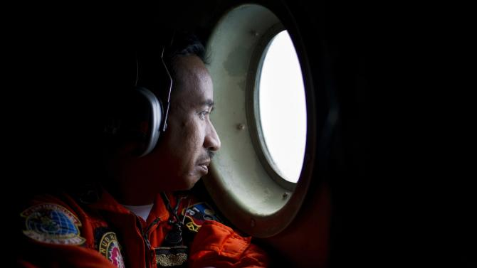 Member of a Hercules C130 aircrew watches through a window while monitoring the Belitung Timur sea during search operations for AirAsia flight QZ8501 near Belitung island