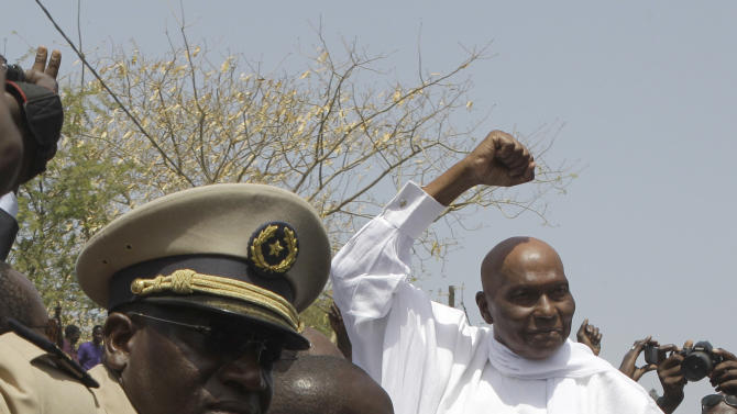 President Abdoulaye Wade is protected by security as he gestures to supporters while leaving a polling station after voting, in his home Point E neighborhood of Dakar, Senegal Sunday, March 25, 2012. Senegalese voters are deciding Sunday whether to give their 85-year-old president another term in office, or instead back his one-time protege Macky Sall in a runoff election that could oust the incumbent of 12 years.(AP Photo/Rebecca Blackwell)