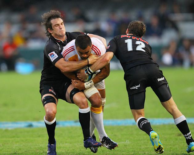 New Zealand Waikato Chiefs' Liam Messam (C) is tackled by Durban Sharks Keegan Daniels (L) during a Super 15 rugby union match at the Mr Price Kings Park Rugby Stadium on April 21, 2012.  AFP PHOTO (P