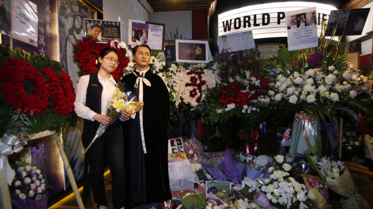 A fan poses besides a wax figure of the late actor-singer Leslie Cheung at Hong Kong's Madame Tussauds Monday, April 1, 2013. Cheung's fans placed flowers to mark the 10th anniversary of the death of Hong Kong screen and singing legend Cheung. (AP Photo/Kin Cheung)