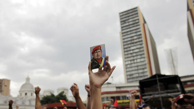 """A """"Chavista"""" demonstrator, and supporter of President-elect Nicolas Maduro, holds a photo of the late President Hugo Chavez during a march in front of the National Electoral Council (CNE) in Caracas, Venezuela, Wednesday, April 17, 2013.  Opposition candidate Henrique Capriles has presented a series of allegations of vote fraud and other irregularities to back up his demand for a vote-by-vote recount for the presidential election. Maduro, the hand-picked successor of the late Hugo Chavez, was declared the winner by 262,000 votes out of 14.9 million cast, and Capriles contends the purported abuses add up to more than Maduro's winning margin. (AP Photo/Ramon Espinosa)"""